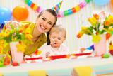 Smiling mom and eat smeared baby on birthday celebration party
