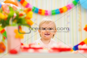 Portrait of eat smeared baby celebrating first birthday