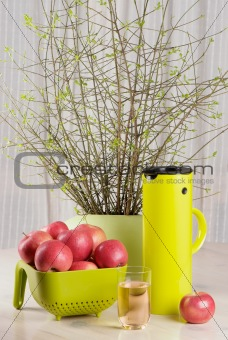apples, glass of juice and thermos jug on the table