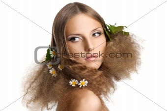 Beauty girl with leaves and camomile in hair
