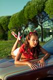 Young woman lay on retro car in summer sunset