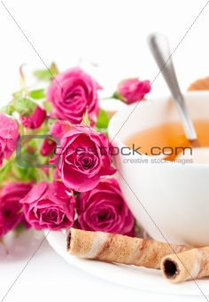 tea in cup with biscuits and bouquet roses