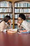 Girls gossiping in library