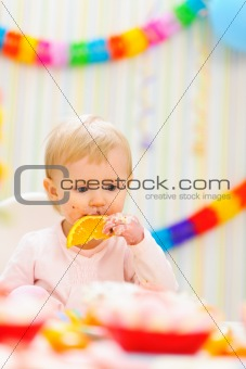 Baby eating orange on first birthday celebration party