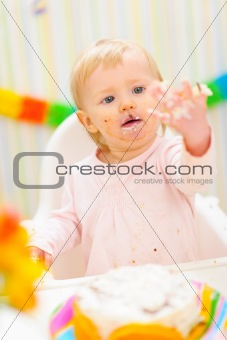 Portrait of baby smeared in birthday cake