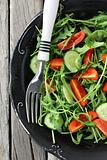 salad with arugula and cherry tomatoes on black vintage plate