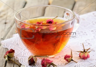 cup of tea with dried roses on a wooden table