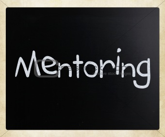"The word ""Mentoring"" handwritten with white chalk on a blackboar"