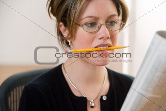 Woman with pencil and newspaper