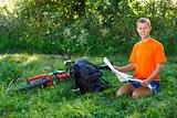 Smiling Man cyclist with map in hand sitting among the green nature