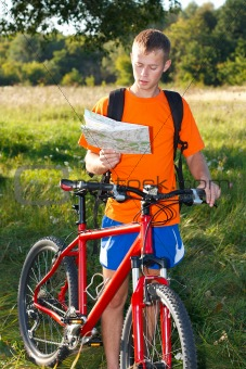 Man cyclist read the map among the summer's nature