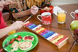 Boy playing xylophone at breakfast table