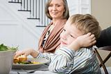 Boy and grandmother having meal