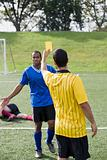 Referee giving yellow card to footballer