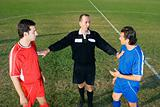 Referee stopping two footballers