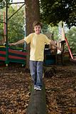 Boy walking on a log