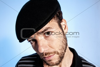 Young modern man portrait handsome hat blue background