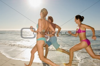 Friends running along beach