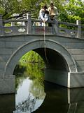 Grandfather son and grandson fishing off bridge