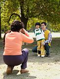 Woman photographing son and grandson