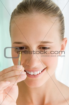 Young woman applying false eyelashes