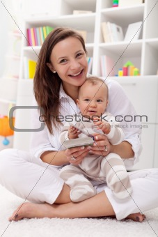 Baby girl reading her first book with mother