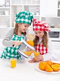 Girls making freshly squezed orange juice