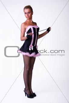 Female model posing in blak and pink dress
