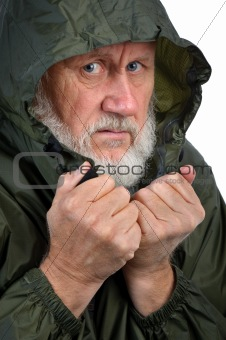 pathetic senior bearded man in green waterproof jacket