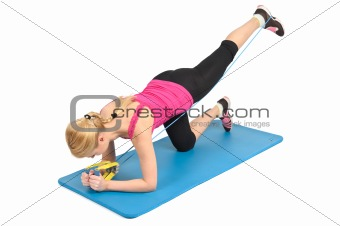 Young blond girl doing kneeling butt blaster exercise using rubber resistance band. position 2 of 2.
