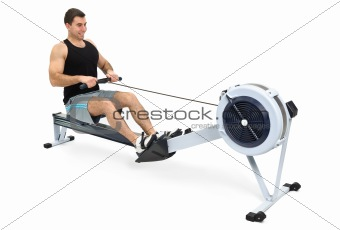 man doing exercises on rowing machine, on white background
