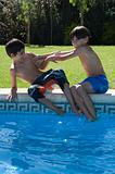 Boys playfighting by pool
