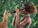 Woman looking at a deer through binoculars