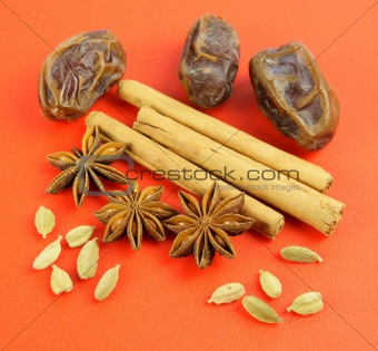 Winter flavors: Cardamom, Cinnamon, star anise, dates on red background