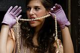 Young woman biting a pearl necklace