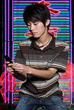 Young man with cellphone by neon sign