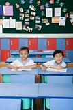 Two children sat at their desks