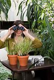 Woman using binoculars in an overgrown office