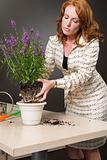 Woman placing a plant on desk