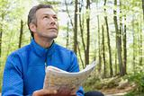 Man using a map in a forest