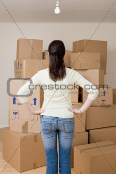 Woman looking at stack of cardboard boxes