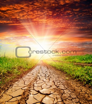 sunset over cracked rural road