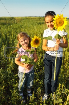 Portrait of two cute little girls with sunflowers