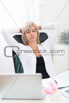 Tired senior business woman looking on computer