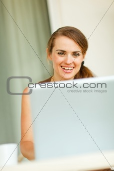 Portrait of young woman working on laptop