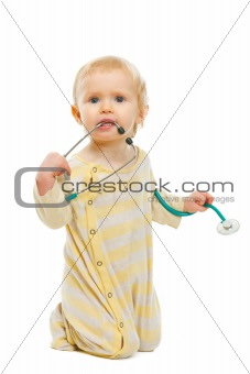 Curious kid playing with stethoscope on white background