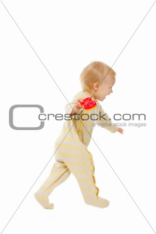 Cheerful baby running with rattle on white background