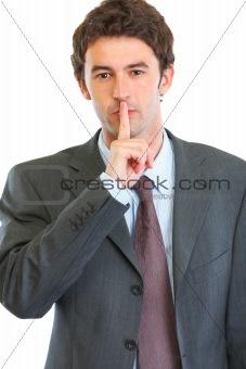 Portrait of modern business man showing shh gesture