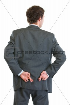 Business man standing back to camera with crossed fingers