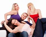 four young friends sitting on sofa smiling, embracing